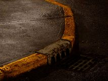 Gutter. A curb on a dark,rain soaked street. A drainage grate on the bottom right stock image