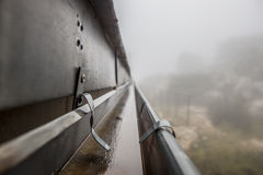 Gutter drainage system on the roof with dripping fog Stock Image