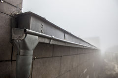 Gutter drainage system on the roof with dripping fog Stock Photos