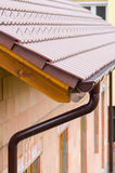 Gutter on house corner. Metal eave on roof royalty free stock photos
