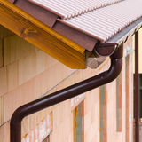 Gutter on house corner. Metal eave on roof stock photography