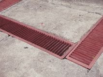Gutter Red Grate Drainage street sewers Storm drain Royalty Free Stock Image