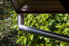 Gutter. Silver metal rain gutter system with wooden decking Stock Photo