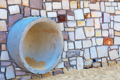 Gutter in a stone wall on the beach Stock Images