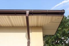 Guttering casero, canales, sistema plástico de Guttering, Guttering y tubo del drenaje exterior contra el cielo azul foto de archivo