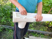Guttering construction. Contractor installing rain gutter downspout drain pipe. Photo stock image