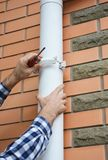 Guttering. Contractor installing rain gutter downspout drain pipe. Close up stock photos
