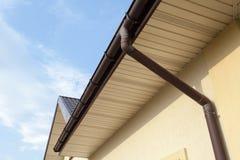 Guttering home, calhas, sistema plástico de Guttering, Guttering & tubulação da drenagem exterior contra o céu azul Foto de Stock Royalty Free