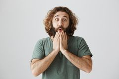 Guy is afraid wife will find out his secret. Portrait of shocked and stunned handsome eastern spouse with curly hair and. Beard holding palms on chin, gasping Royalty Free Stock Photography