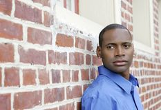 Guy against brick wall Stock Image