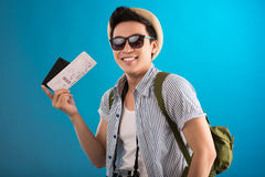 Guy with air ticket. Portrait of a cheerful guy with an air ticket in hand smiling and looking at camera isolated on blue Stock Photography