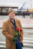 The guy at the airport with roses Royalty Free Stock Photos