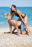 Guy on all fours biting pear in girl`s hands. Attractive couple flirting on beach. Guy on all fours biting the pear in the girl`s hands stock image