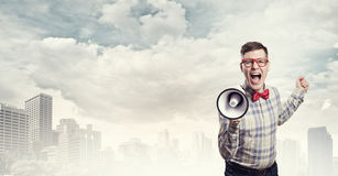 Guy announcing something. Young funny man screaming emotionally in megaphone Stock Images