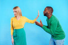 Guy is apologizing to girl. Please forgive me. Guilty young african men is asking sorry in girlfriend. Abused women is raising hand while showing stop sign Stock Photo