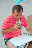 The guy-artist drinks a brown drink Royalty Free Stock Images