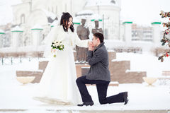 Guy asks the girl hands. Winter wedding, groom on his knee in front of the bride a snowy street. The marriage concept. The guy asks the girl hands. Winter Royalty Free Stock Photo
