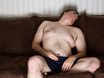 Guy asleep on the couch royalty free stock photography