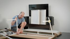 Guy is assembling a furniture himself in a room, installing long white beams on a carcass of modern table. Sitting on a floor stock video footage