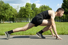 Guy athlete starts on the path in the park Royalty Free Stock Image