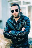 Guy with attitude wearing leather jacket and sunglasses out. Sexy guy with attitude wearing leather jacket and sunglasses outdoors Royalty Free Stock Image