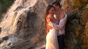 A guy attracts a girl standing among the rocks under the waterfall during the sunset, slow motion stock video