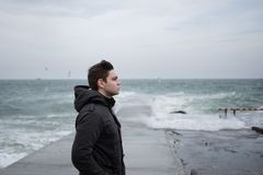 Guy on the background of the sea looking into the distance. A handsome young guy on the background of the sea stands in the wind and gazes into the distance Royalty Free Stock Image