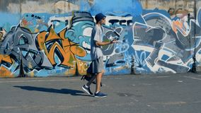 A male graffiti artist walks along a painted wall. A guy with a backpack walks along a graffiti wall and plays with a paint can stock video