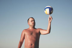 Guy with the ball. Young man on the beach playing in his vacation, he is balancing the ball on his fingertip Royalty Free Stock Photo