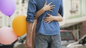 Guy with balloons waiting for date, girl approaching and hugging him, meeting. Stock footage stock video footage
