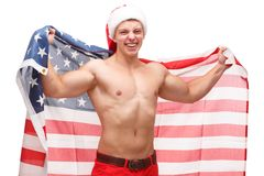 A guy with bare chest tipped the American flag behind his back on white isolated background stock photo