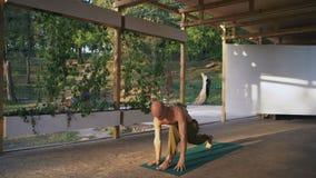 Guy Barefoot novo e com o torso despido executa a ioga Asanas no Pomo de madeira no parque da cidade video estoque