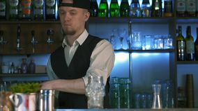 Guy-bartender starts his master class of preparation an alcohol cocktail. The process of preparation delicious alcoholic cocktail. Barmen tells on camera in stock video
