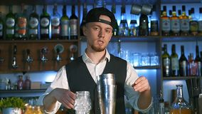 Guy-bartender starts his master class of preparation an alcohol cocktail. Barmen tells on camera in slow motion stock video