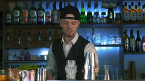 Guy-bartender starts his master class of preparation an alcohol cocktail. The process of preparation delicious alcoholic cocktail. Barmen tells on camera in stock video footage