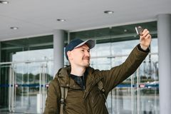 A guy in a baseball cap or a tourist photographs or does selfie on the phone. Royalty Free Stock Photos