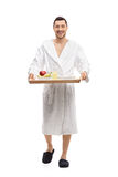 Guy in a bathrobe carrying a tray and walking royalty free stock images