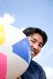 Guy with beach ball - smiling Stock Image