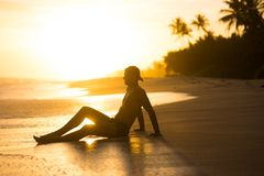 Guy on the beach at sunset in the tropics of asia. bright sun in the evening above the beach. silhouette on the glare Royalty Free Stock Photos