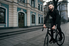 Guy with beard in black clothes rides fix bike Stock Photos