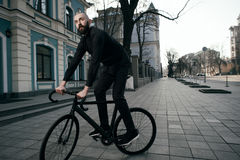 Guy with beard in black clothes rides fix bike Royalty Free Stock Photography