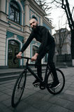 Guy with beard in black clothes rides fix bike Royalty Free Stock Image
