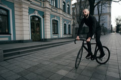Guy with beard in black clothes rides fix bike Stock Image