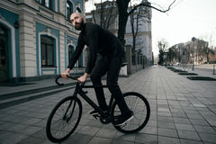Guy with beard in black clothes rides fix bike Royalty Free Stock Photo