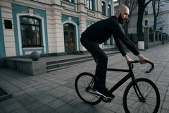 Guy with beard in black clothes rides fix bike Royalty Free Stock Photos
