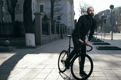 Guy with beard in black clothes rides fix bike Stock Photography