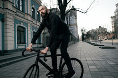 Guy with beard in black clothes rides fix bike Stock Photo