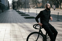Guy with beard in black clothes sits on fix bike Royalty Free Stock Photo