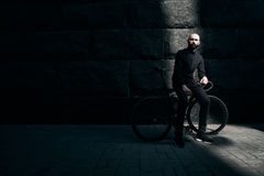 Guy with beard in black clothes sits on fix bike Royalty Free Stock Images