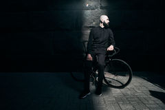 Guy with beard in black clothes sits on fix bike Stock Photography